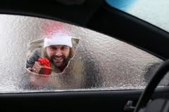 Hombre en un casquillo rojo de Santa Claus en un coche con el vidrio quebrado Imagenes de archivo