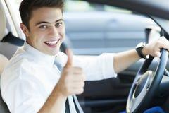 Hombre en un coche con los pulgares para arriba Imágenes de archivo libres de regalías