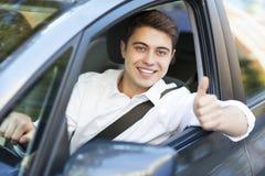 Hombre en un coche con los pulgares para arriba Foto de archivo libre de regalías