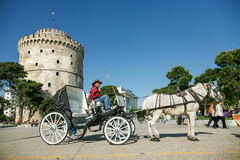 Hombre en un coche del caballo cerca de la torre blanca en Salónica Foto de archivo libre de regalías