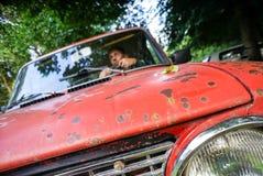 Hombre en un coche rojo Fotos de archivo