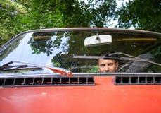 Hombre en un coche rojo Imagen de archivo