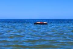 Hombre en un colchón inflable en el mar Imágenes de archivo libres de regalías