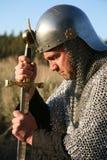 Hombre en un correo de cadena que se arrodilla y que aprieta una espada Imagen de archivo