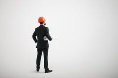 Hombre en un desgaste formal y en un casco que sostiene modelos Fotografía de archivo