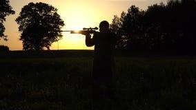 Hombre en un fondo de la puesta del sol con la cámara lenta del arma metrajes