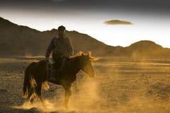 Hombre en un horese contra puesta del sol foto de archivo