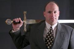 Hombre en un juego con la espada lanzada con una honda sobre hombro Foto de archivo libre de regalías