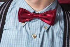 Hombre en un juego rojo y una camisa de tela escocesa de la pajarita Imágenes de archivo libres de regalías