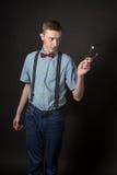 Hombre en un juego rojo y una camisa de tela escocesa de la pajarita en un fondo negro Fotografía de archivo libre de regalías