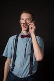 Hombre en un juego rojo y una camisa de tela escocesa de la pajarita en un fondo negro Fotografía de archivo