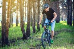 Hombre en un montar a caballo del casco en una bici de montaña en el bosque Ciclista en el movimiento Concepto de forma de vida a imagenes de archivo