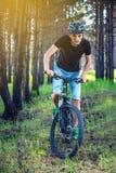 Hombre en un montar a caballo del casco en una bici de montaña en el bosque entre los árboles Ciclista en el movimiento Forma de  fotografía de archivo libre de regalías