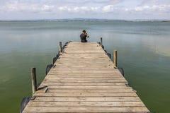 Hombre en un muelle por el lago en el cielo de la mañana imagen de archivo