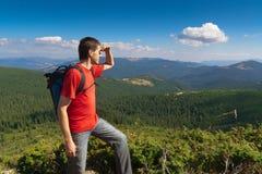Hombre en un pico de montañas y de mirar el paisaje Foto de archivo libre de regalías