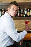 Hombre en un pub con esperar de martini Imagen de archivo libre de regalías