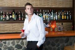 Hombre en un pub con martini rojo Fotos de archivo libres de regalías