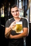 Hombre en un pub o una barra que sostiene la taza la cerveza alta en el aire para las alegrías Fotos de archivo