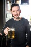 Hombre en un pub o una barra que sostiene la taza la cerveza alta en el aire para las alegrías Fotografía de archivo