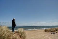 Hombre en un punto de vista que pasa por alto una playa Fotografía de archivo libre de regalías