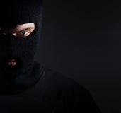 Hombre en un retrato del pasamontañas, ladrón en un fondo oscuro Foto de archivo libre de regalías