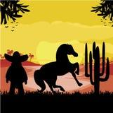 Hombre en un sombrero y su caballo en puesta del sol del desierto Imágenes de archivo libres de regalías