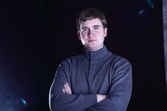 Hombre en un suéter en el fondo negro foto de archivo libre de regalías