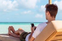 Hombre en un sunchair en una ubicación tropical usando su smartphone Agua clara de la turquesa como fondo fotos de archivo