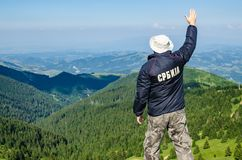 Hombre en un top de la montaña Traducción del texto en la chaqueta: imágenes de archivo libres de regalías
