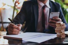 Hombre en un traje de negocios formal usando un smartphone al aire libre Fotos de archivo libres de regalías