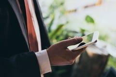 Hombre en un traje de negocios formal usando un smartphone al aire libre Foto de archivo libre de regalías