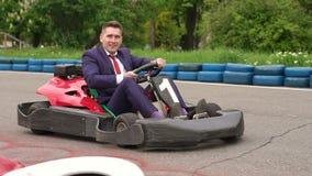 Hombre en un traje que conduce el coche del kart en un patio almacen de metraje de vídeo
