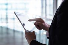 Hombre en un traje usando la tableta Hombre de negocios con el dispositivo móvil elegante foto de archivo libre de regalías