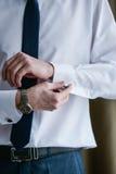 Hombre en un tux que fija su mancuerna imagen de archivo libre de regalías