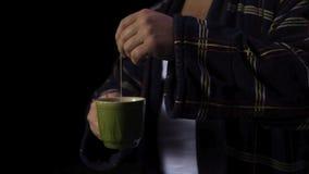 Hombre en una albornoz con una taza de té existencias Un hombre hace té en un fondo negro Mún concepto del humor imagen de archivo
