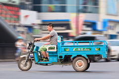 Hombre en una bici eléctrica de la carga en Pekín céntrica, China Imagenes de archivo