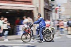 Hombre en una bici eléctrica que pasa una tienda, Shangai, China Fotos de archivo libres de regalías