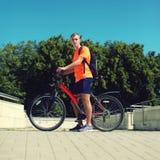 Hombre en una bicicleta en día de verano sobre el cielo azul, ciclista masculino en perfil Foto de archivo