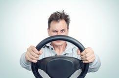 Hombre en una camiseta blanca con el volante, en fondo concepto del conductor de coche imagen de archivo libre de regalías