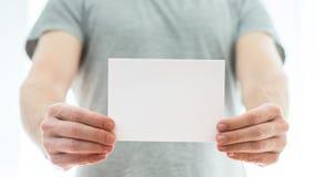 Hombre en una camiseta gris que sostiene una tarjeta en blanco Imagen de archivo