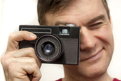 Hombre en una camiseta roja con la cámara vieja Foto de archivo libre de regalías