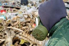 Hombre en una careta antigás que mira la basura imágenes de archivo libres de regalías