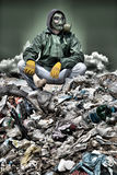 Hombre en una careta antigás que se sienta en la basura y que sostiene un hueso fotos de archivo