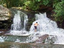 Hombre en una cascada Imágenes de archivo libres de regalías