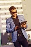 Hombre en una chaqueta a cuadros con la tableta Imágenes de archivo libres de regalías