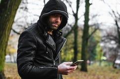 hombre en una chaqueta de cuero con una barba con la capilla Fotos de archivo