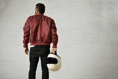 Hombre en una chaqueta del piloto de Burdeos con el casco Foto de archivo libre de regalías