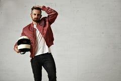 Hombre en una chaqueta del piloto de Burdeos con el casco Fotos de archivo libres de regalías