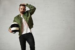 Hombre en una chaqueta experimental de color caqui con el casco Imagenes de archivo