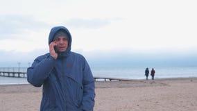 Hombre en una chaqueta en la playa por el mar en invierno que habla en un teléfono móvil metrajes